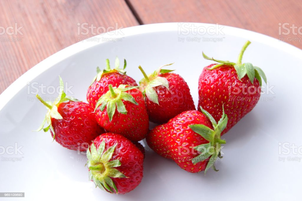 Strawberries on a white plate top view, red berries on a wooden background, fresh strawberries on dark wooden boards, vegetarian food royalty-free stock photo