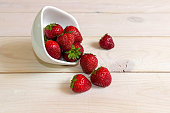 Strawberries on a white wooden background. Summer background. White plate.
