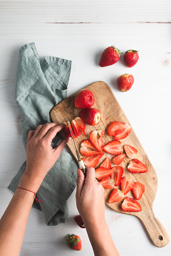 Strawberries on cutting board, with knife and plate