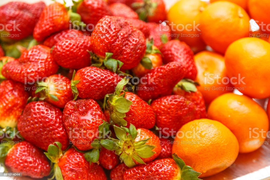 Strawberries, oranges and other fruit are on a plate on a festive table. royalty-free stock photo
