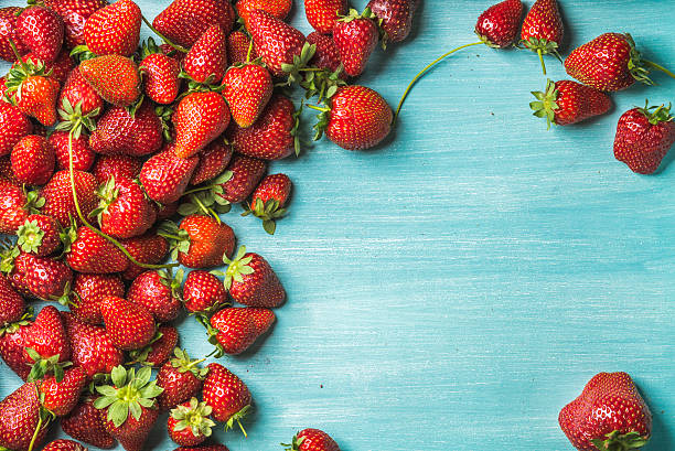 Strawberries over turquoise blue painted wooden background foto