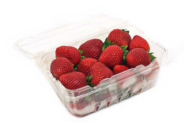 Strawberries Fresh, ripe strawberries in clear plastic container isolated on white background in horizontal format fruit carton stock pictures, royalty-free photos & images