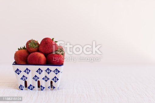 A bright photo of deep Red Strawberries in square baskets.