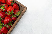 Fresh strawberries in a wood container on the white background.