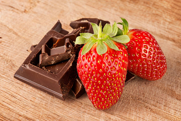 Strawberries with chocolate bar in pieces stock photo