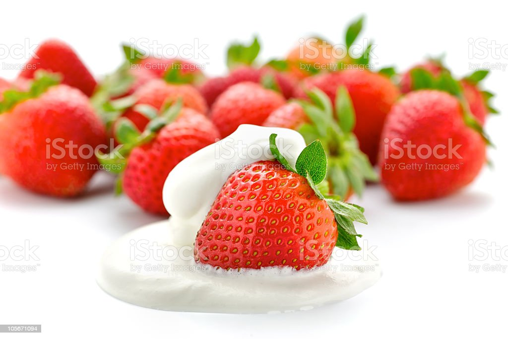 Strawberries with one in whipped cream stock photo