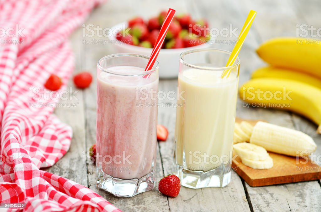 Strawberry and banana milkshake smoothie in the glass with straw stock photo