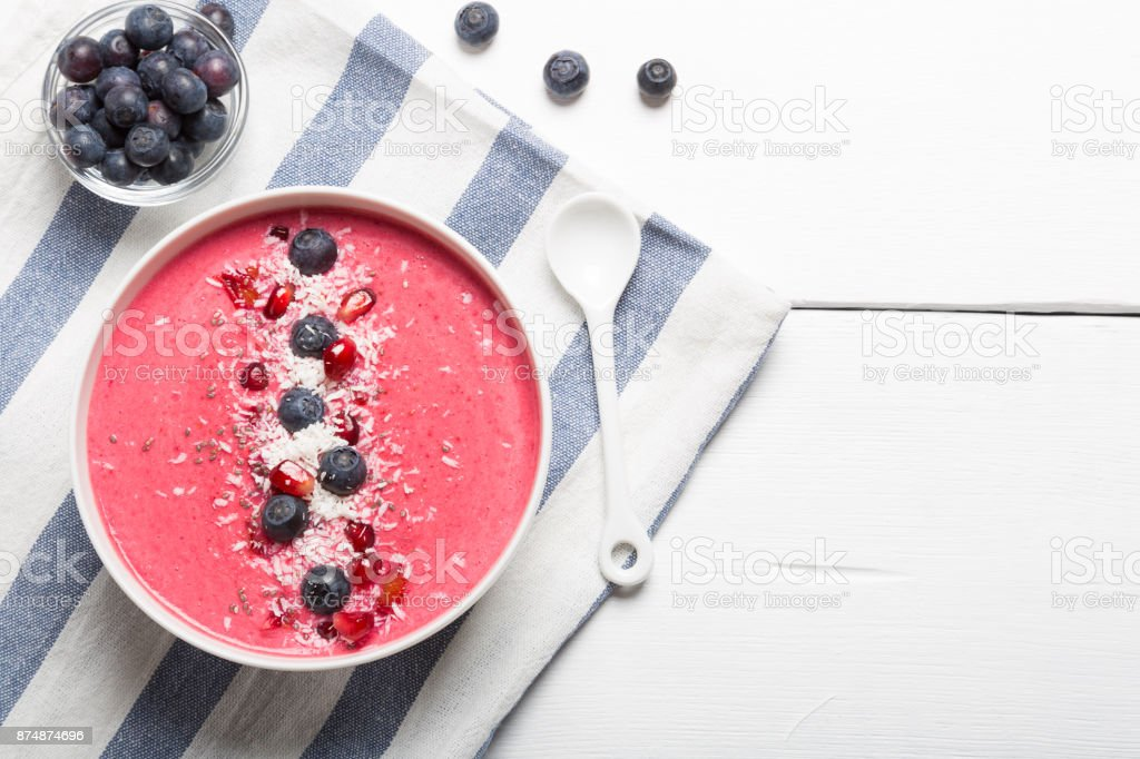 Strawberry and beetroot smoothie bowls topped with blueberries, pomegranate seeds and shredded coconut on a white and blue striped clothe. Top view copy space stock photo