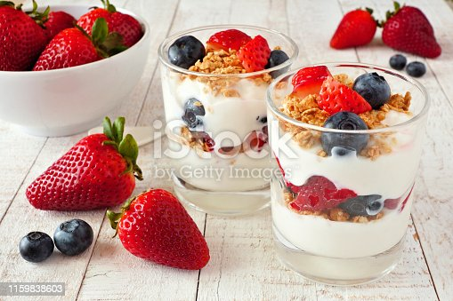 Strawberry and blueberry parfaits in glasses against a bright white wood background