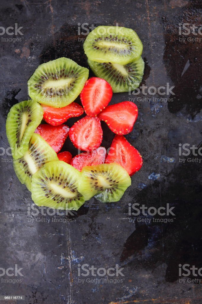 Strawberry and kiwi on a dark metallic background, red berries and sliced kiwi on a vintage background, vegetarian food, red and green fruit top view zbiór zdjęć royalty-free