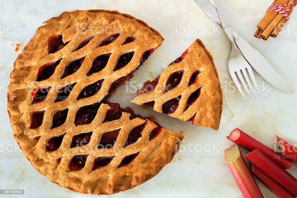 Strawberry and rhubarb pie with slice on marble background stock photo