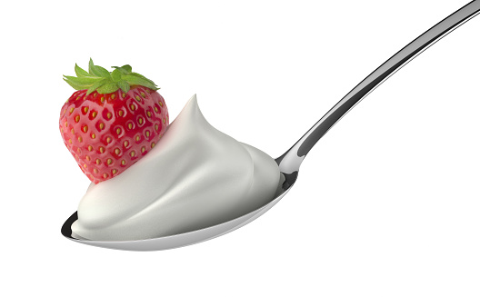 Strawberry on top of white cream on a spoon