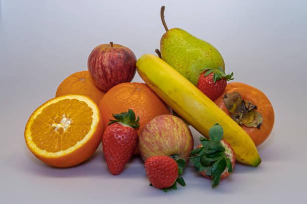 erdbeere, apfel, banane, rock pear, orange, persimmon. abwechslungsreiche früchte, die für eine gesunde und ausgewogene ernährung unerlässlich sind. - immunsystem stärken stock-fotos und bilder