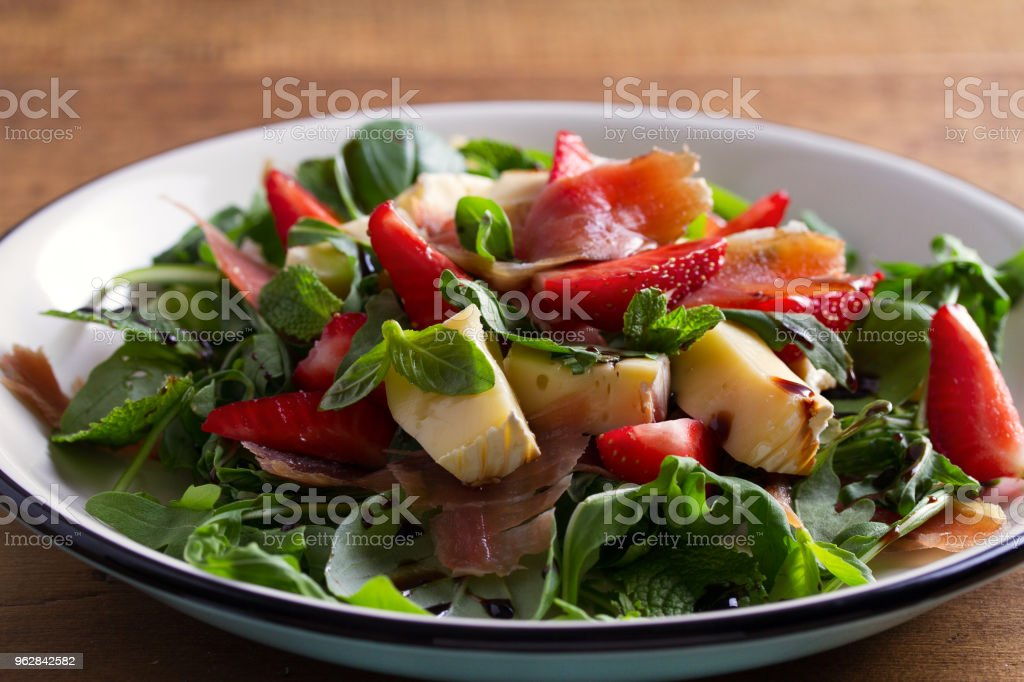Strawberry, avocado, basil, mint, arugula salad with brie cheese and jamon or prosciutto stock photo