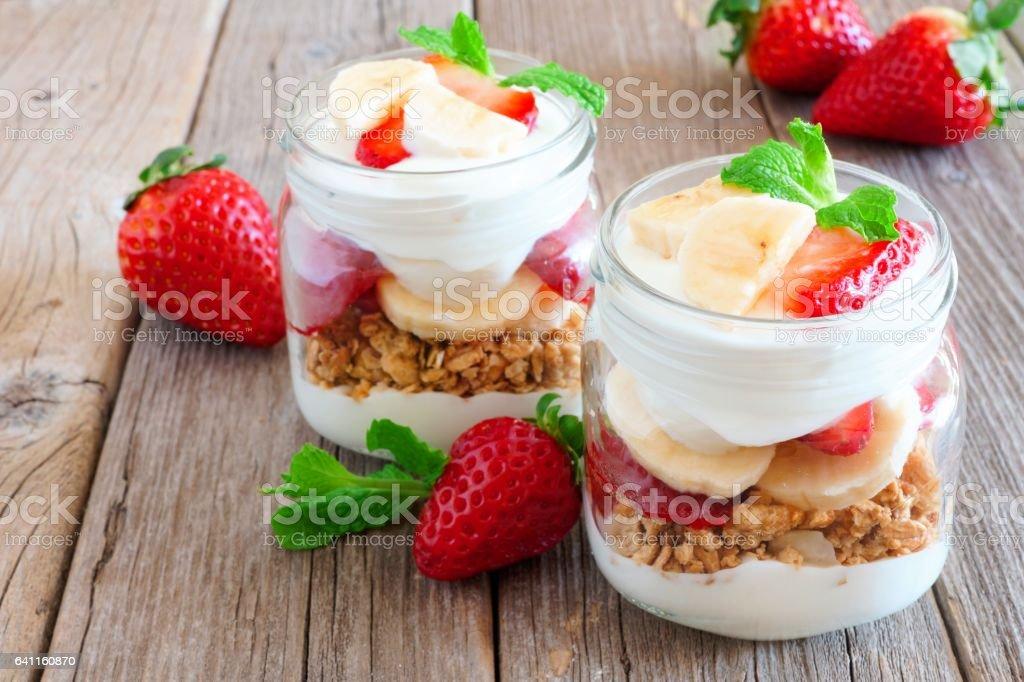 Strawberry banana parfaits in mason jars on rustic wood stock photo