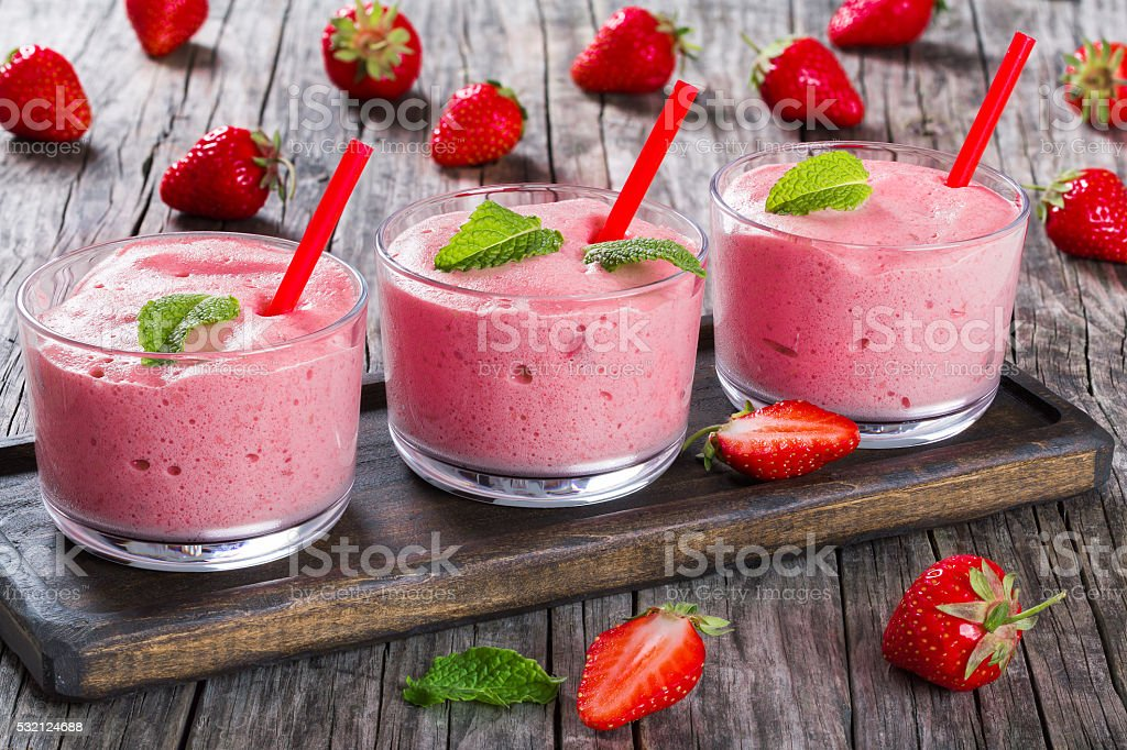 Strawberry Banana Smoothies Cups with straws and mint leaves stock photo
