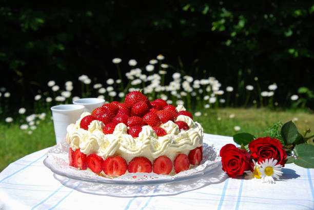 Strawberry cake and two mugs on a garden table stock photo