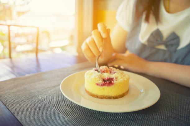 erdbeer-käsekuchen mit hand löffel krepp soße auf weißen teller. crêpe kuchen zum nachtisch kaffee shop.vintage farbe - regenbogen käsekuchen stock-fotos und bilder