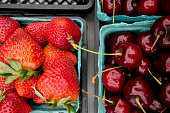 A variety of strawberries and cherries in pint baskets