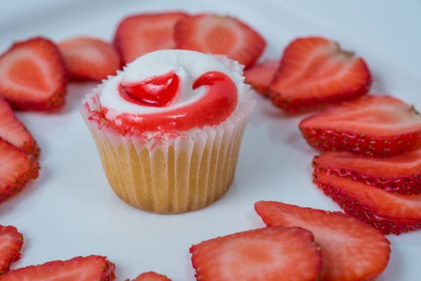 A strawberry cupcake with strawberry slices on white background stock photo