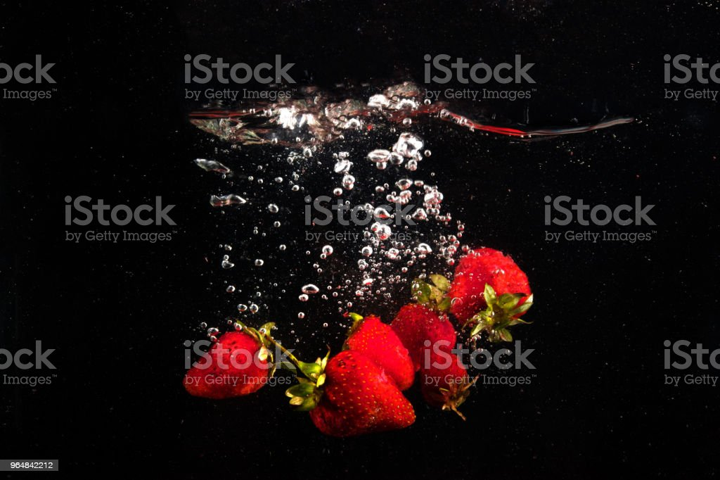 Strawberry dropped into water royalty-free stock photo