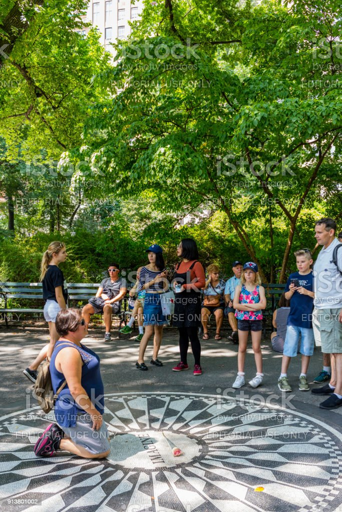 Strawberry Fields Memorial, Central Park. A woman is getting photographed kneeling on the site where John Lennon was killed stock photo