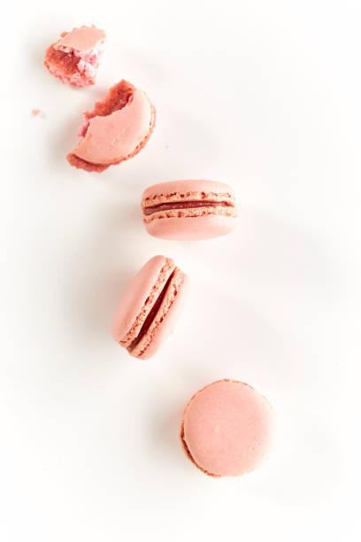 biscoitos com sabor morangos em uma mesa branca e fundo realçado, um com uma mordida - macaroon - fotografias e filmes do acervo