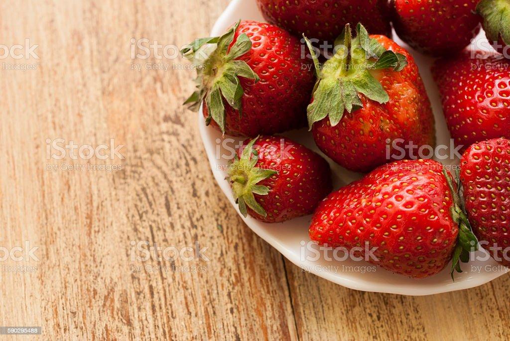 Strawberry fruit lying on a white plate. royaltyfri bildbanksbilder