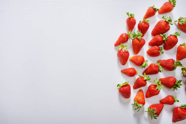 strawberry fruits on the right side on wooden background with copy space. View from above. stock photo