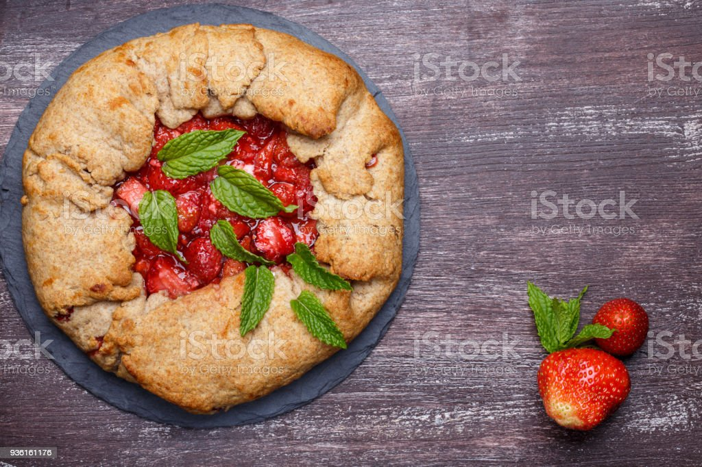 Strawberry galette. Homemade healthy wholegrain berry open pie. Fruit tart. Top view. stock photo