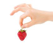 イチゴの手。白で隔離赤い爪を持つ女性の手でイチゴの有機食品