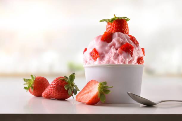 在廚房自製的白色桌子上的草莓霜淇淋杯 - 冷凍乳酪 個照片及圖片檔