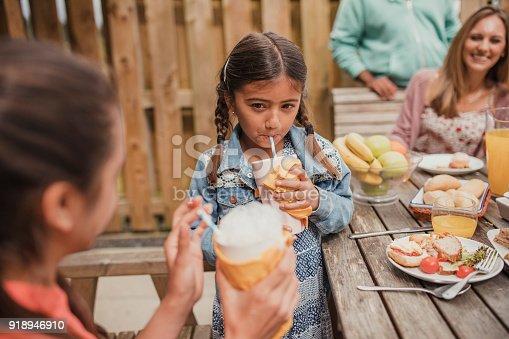 Little girl enjoying a strawberry icecream milkshake outside in summer.