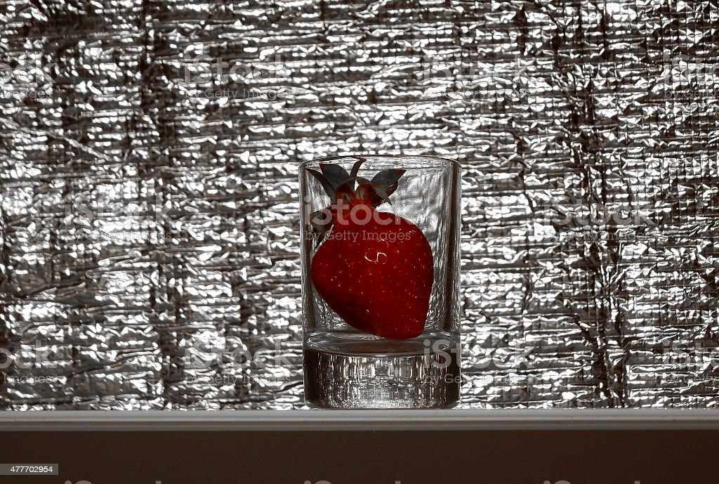 Strawberry in glass on reflective background stock photo