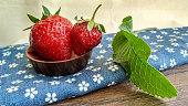 Two juicy red strawberries in cute small wooden bowl with green leaves on the wooden and blue material background in rustic, village, rural style. Healthy seasoning food with vitamins.