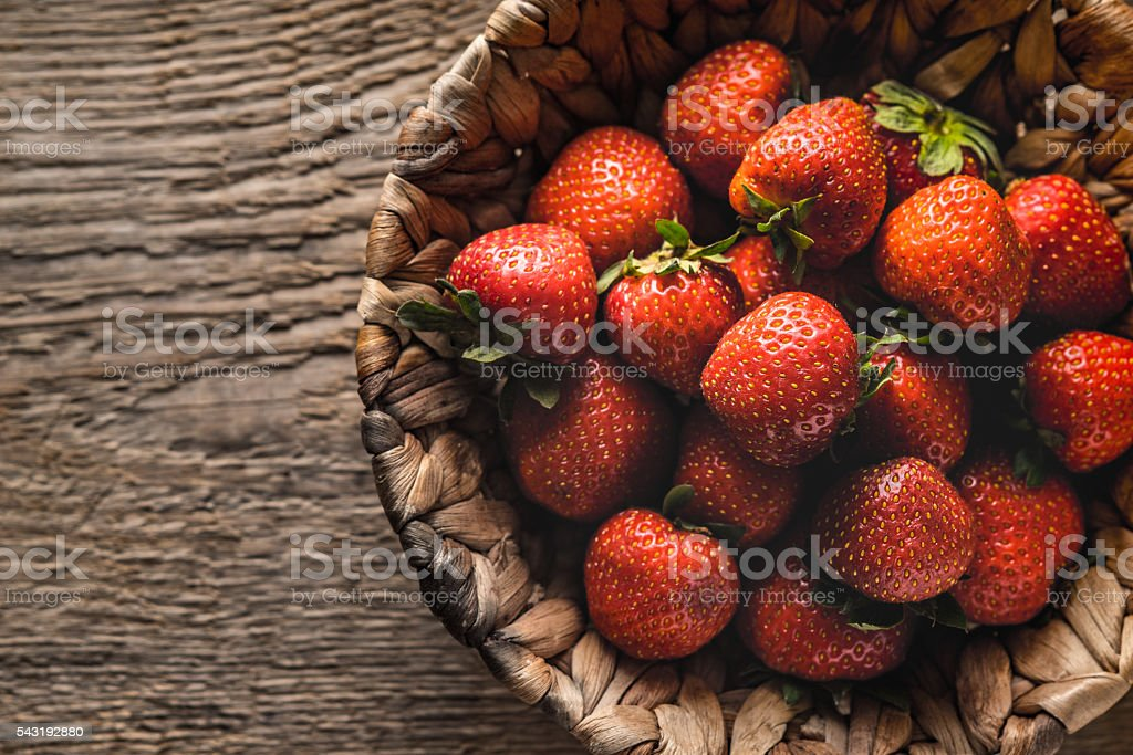 Strawberry in the wicker bowl on wooden table top view Lizenzfreies stock-foto