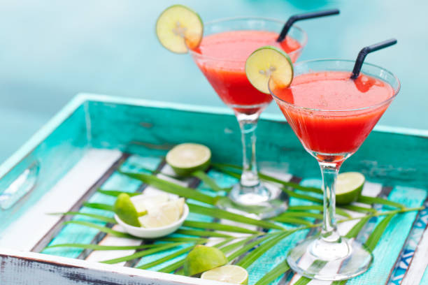 strawberry margarita cocktail on colorful wooden background with palm leaf. copy space - margarita drink stock photos and pictures