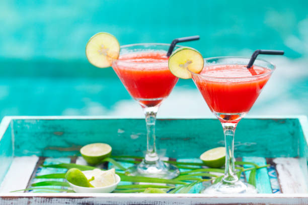 strawberry margarita cocktail on colorful wooden background with palm leaf. copy space. - margarita drink stock photos and pictures