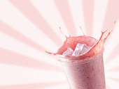 cold strawberry milkshake or smoothie with ice in disposable plastic glass on pink background