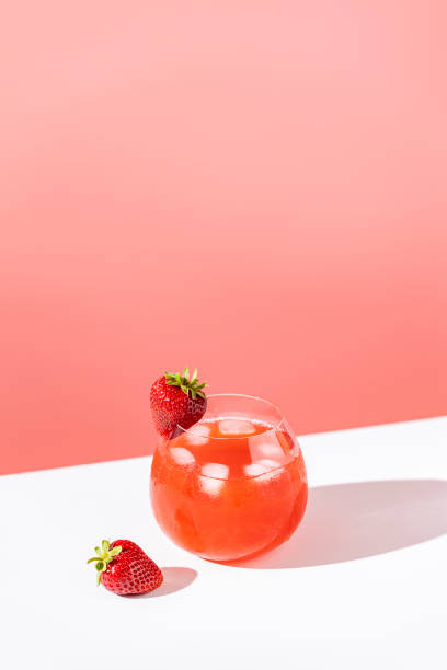 Strawberry mojito cocktail with ice in brandy glass with water drops  on pastel soft pink color background in bright sun light, white board. Copy space, summer vacation and party concept stock photo