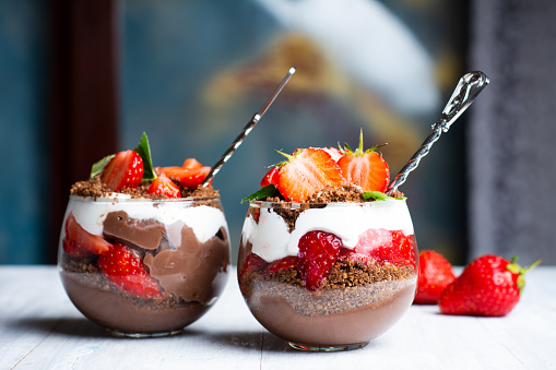 Strawberry parfait dessert in a glass cup with cream and chocolate closeup
