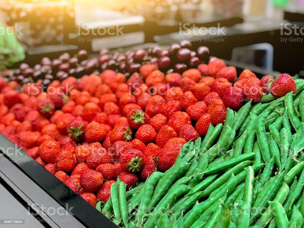 Strawberry, peas, cherries on the counter in the store stock photo