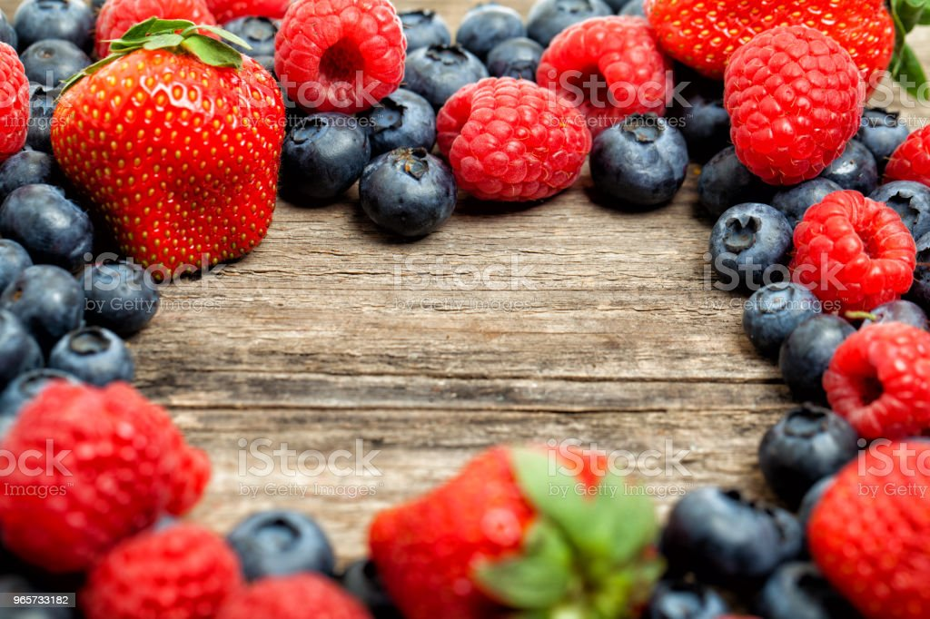 Strawberry, raspberry and blueberries on wooden board background. Healthy eating, frame of assorted berries - Royalty-free Berry Stock Photo