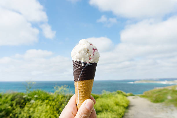 strawberry ripple ice cream at the coast. - ice cream cone stock pictures, royalty-free photos & images