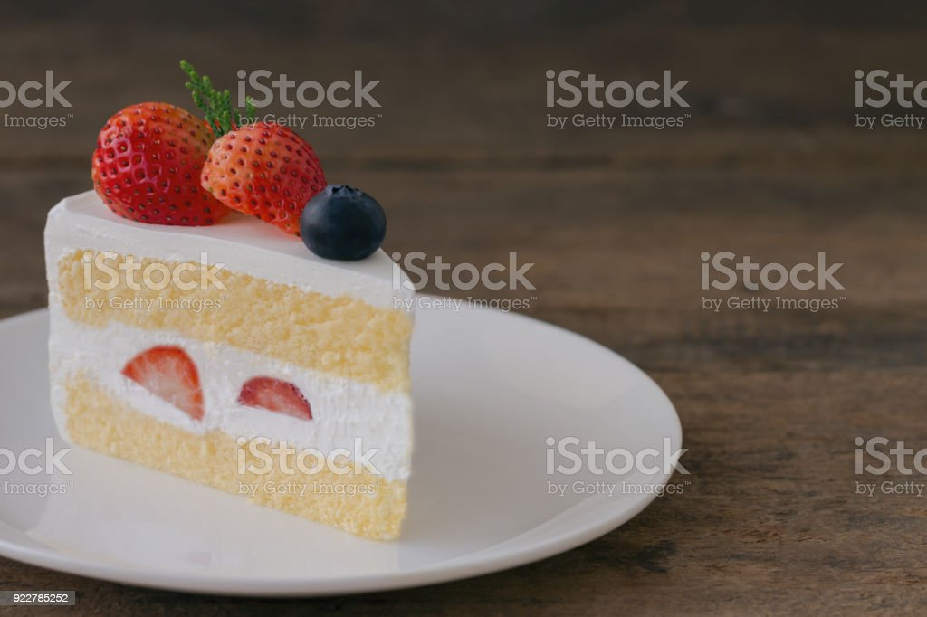 Strawberry shortcake on white plate put on wood table with copy space. Delicious and soft vanilla sponge cake with dairy whipped cream and fresh strawberries and blueberry. Homemade bakery concept. stock photo
