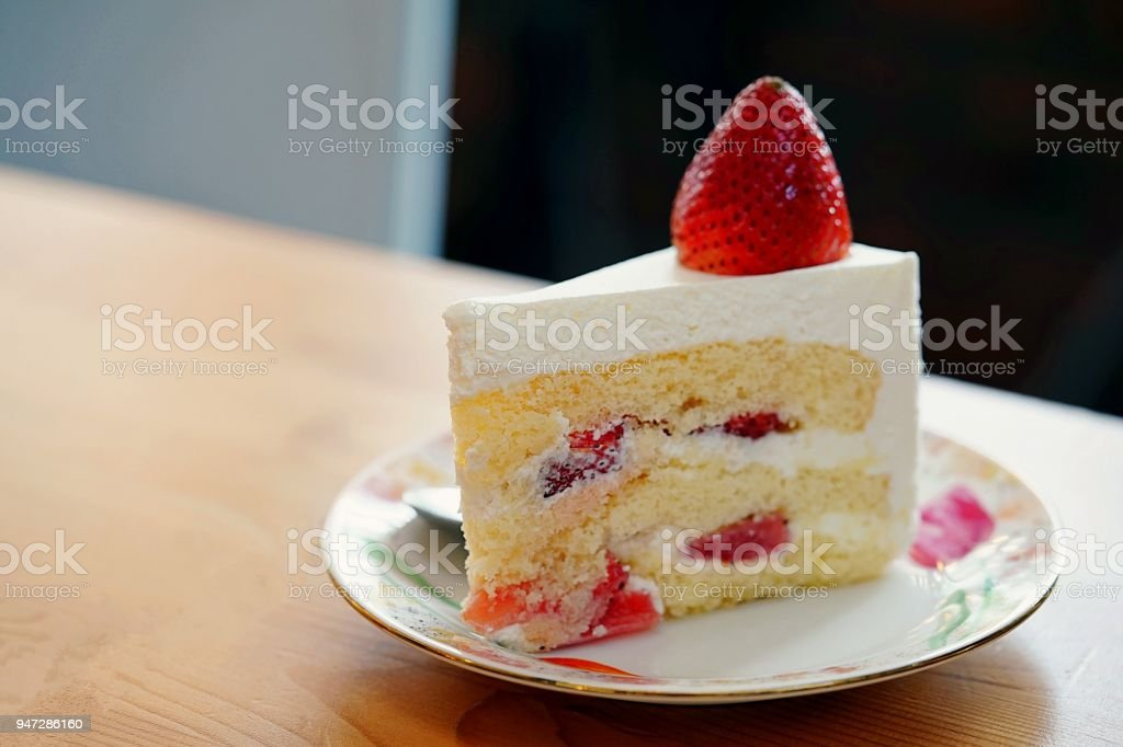 A strawberry shortcake topped with a large fresh strawberry placed in white plate and on wooden table with copy space.Victorian sponge cake - fotografia de stock
