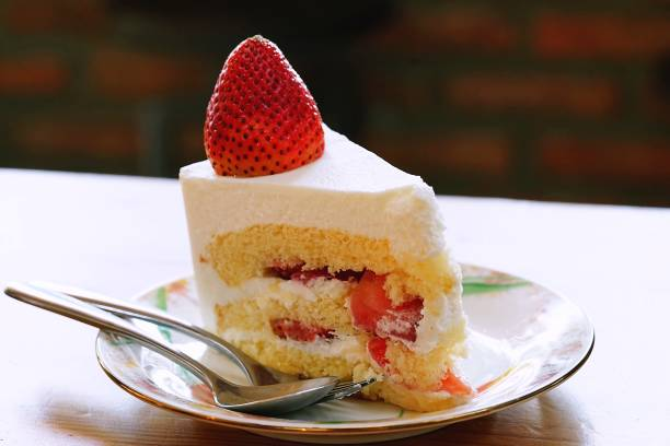 A strawberry shortcake topped with a large fresh strawberry placed in white plate and on wooden table with cafe environment.Victorian sponge cake. - fotografia de stock