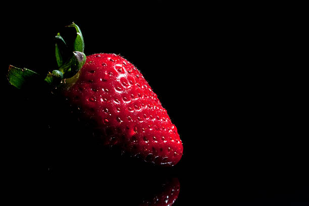 Strawberry single with drops isolated on black stock photo