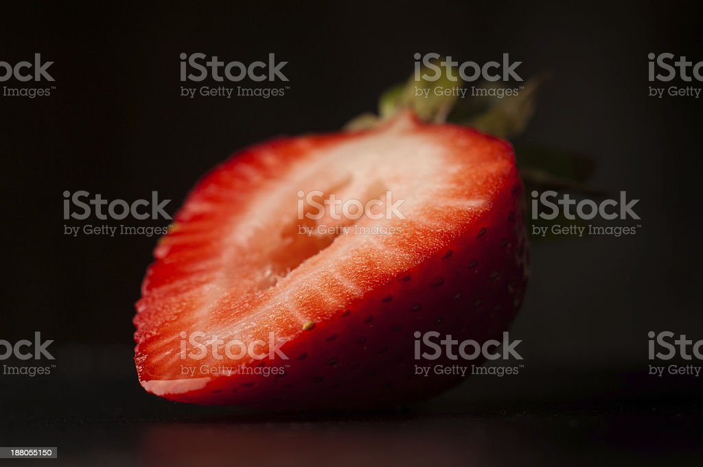 Strawberry slice on black stock photo