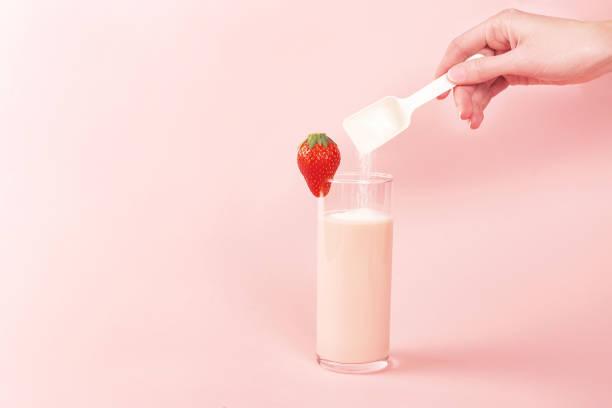 Erdbeer-Smoothie und ein Löffel mit Kollagenpulver oder Protein. – Foto